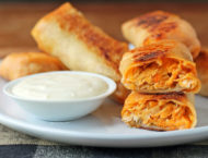 Buffalo Chicken Egg Rolls stacked on a plate