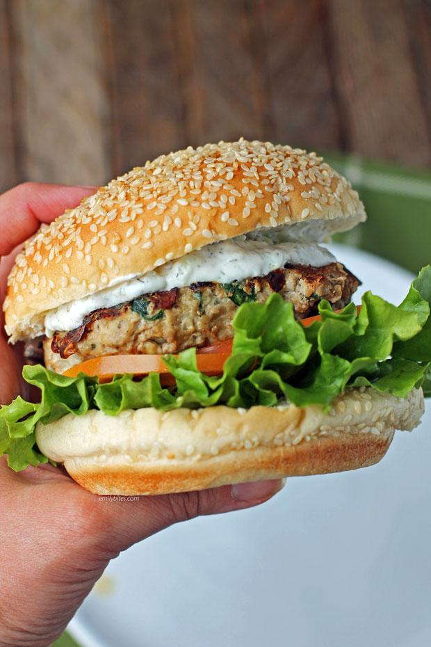 Hand golding a Greek turkey burger